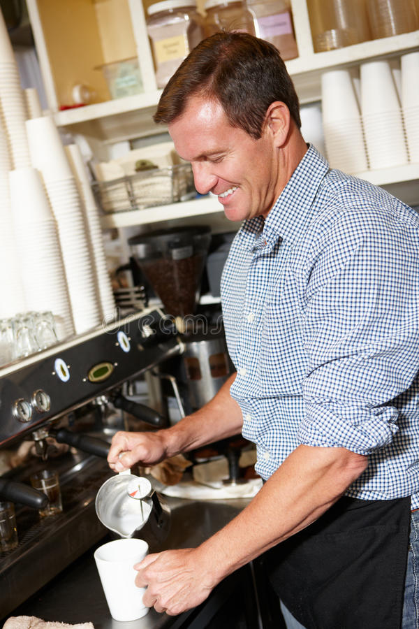 Man working in coffee shop stock image