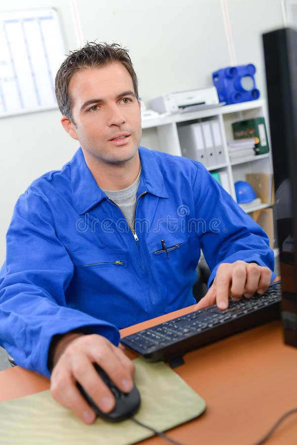 Man on working on computer stock photography