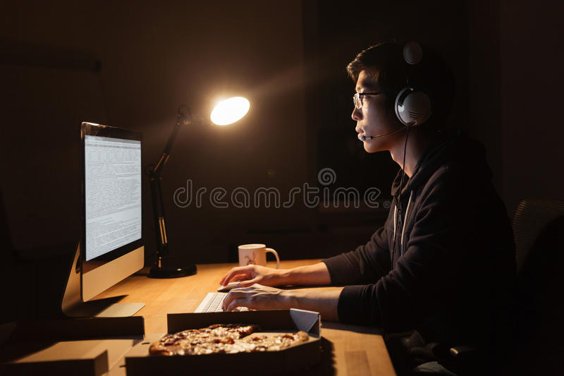 Man working with computer and eating pizza in dark office royalty free stock photos