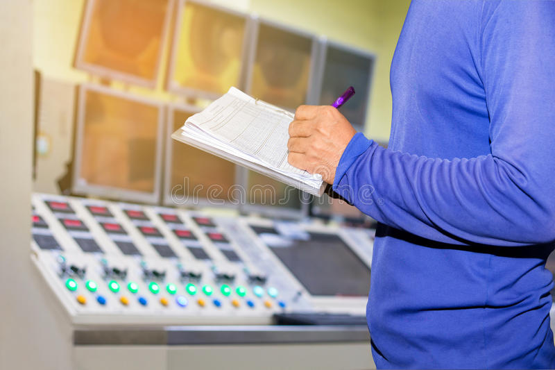 man working in control room,writing and watch monitor on control royalty free stock image