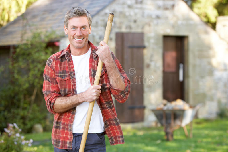 Man working in country garden. Smiling stock image