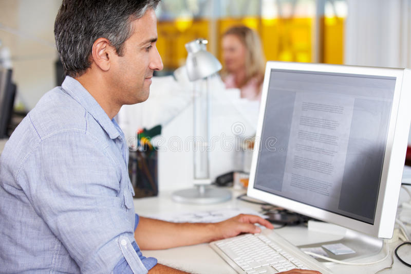 Man Working At Desk In Busy Creative Office stock image