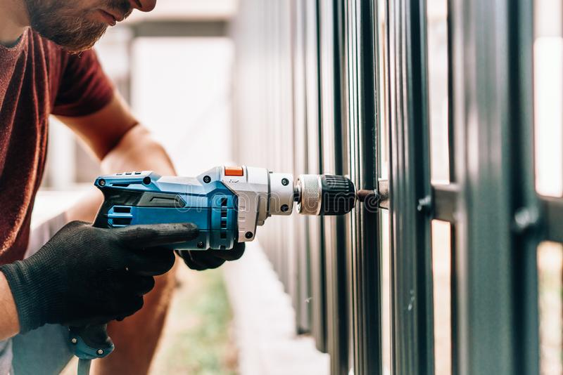 Caucasian man working with an electric screwdriver on the construction site royalty free stock photo