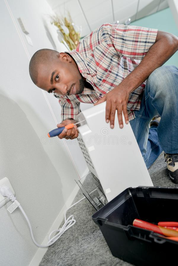 Man working on electrical appliance stock photography