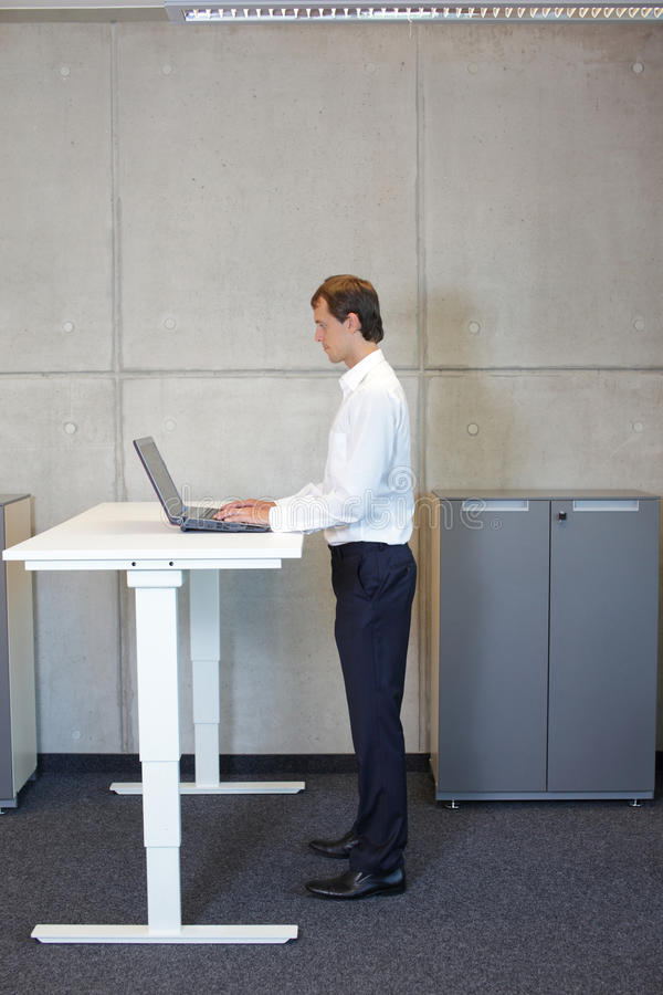 Man working at electrically controlled height adjustment table. Business man in white shirt standing at electrically controlled height adjustment table, working stock photography