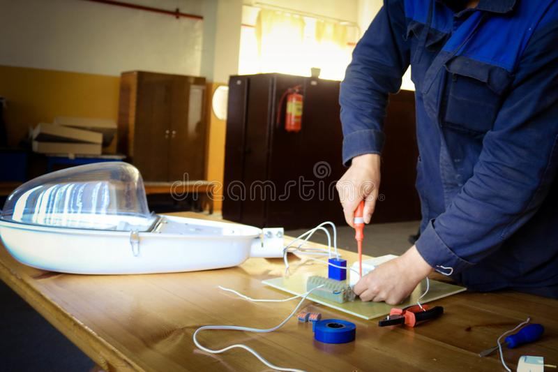 A man working electrician works, collects the electric circuit of a large white street lamp with wires, a relay at an industrial royalty free stock photo
