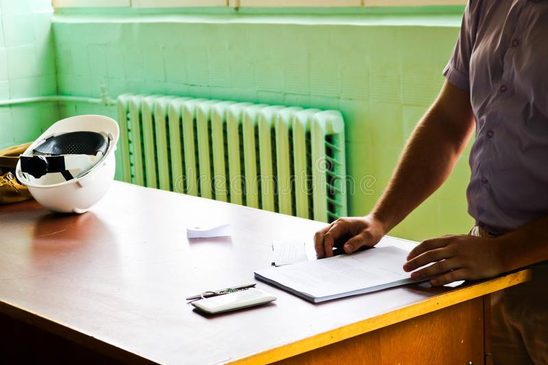 A man working engineer with a white helmet on the desk learns to write in a notebook royalty free stock image