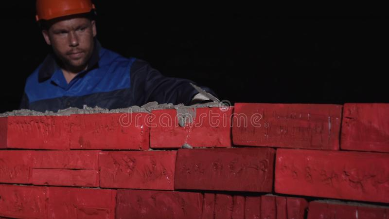 Man in working equipment builds a wall of brick. Stock. Concept of self-development. To build a career, to himself, to stock image