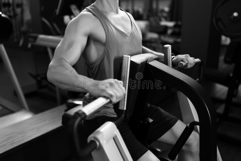 Man working on fitness machine at gym. Man working on fitness machine at the gym stock image