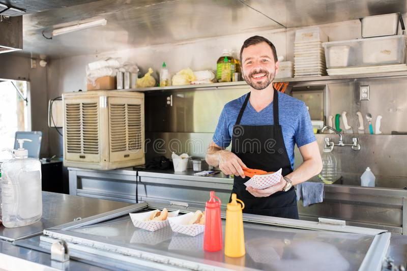 Man working in a food stand. Portrait of a good looking Hispanic man preparing some hot dogs in a food stand and smiling stock photos