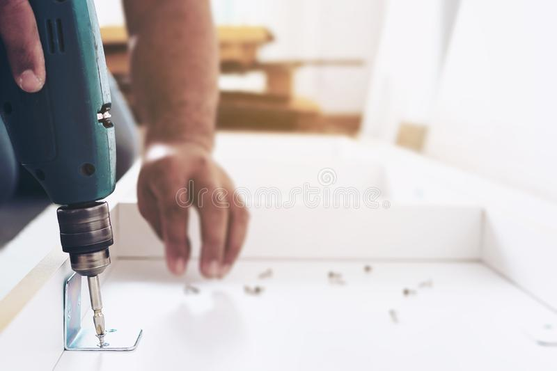 Man is working with furniture assembly using electric screwdriver in new house installation. Technician onsite work using hand tools concept royalty free stock image
