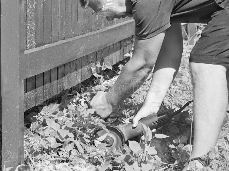 Working with electric circular saw. A man working in a garden with electric circular saw, in black white stock photos