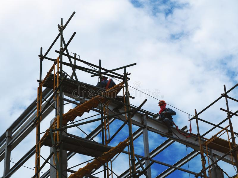 Man Working on the Working at height. On blue sky royalty free stock photo