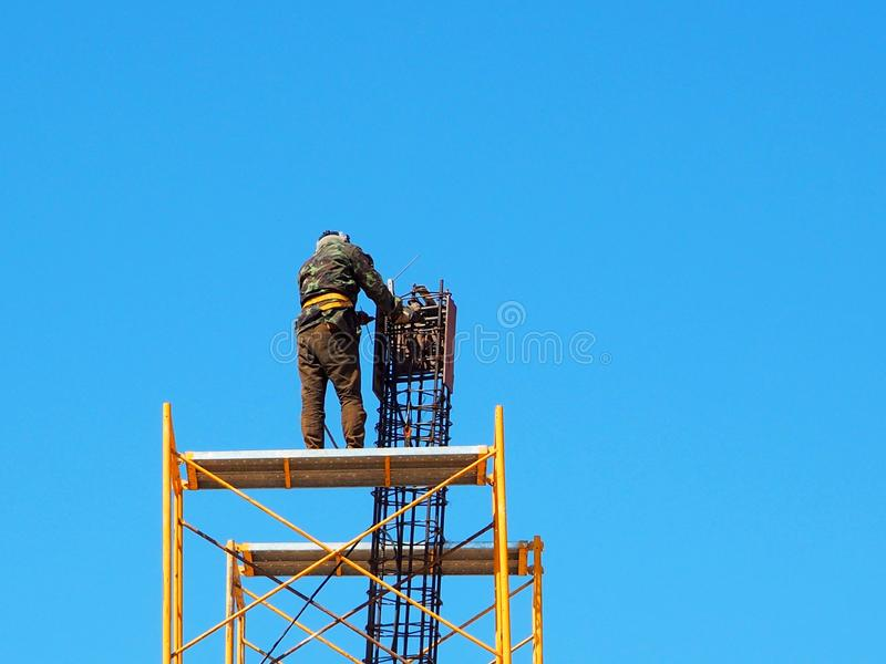 Man Working on the Working at height. On blue sky royalty free stock image