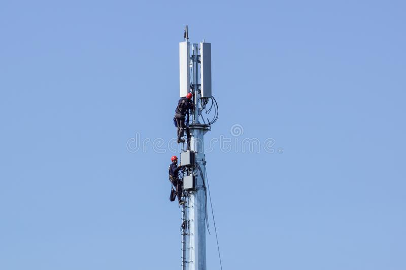 MILAN, ITALY 4 MAY 2019.: man working on high tower or pole of telecommunication. Working with high risk. Maintenance on royalty free stock photos