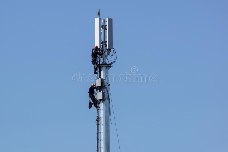 MILAN, ITALY 4 MAY 2019.: man working on high tower or pole of telecommunication. Working with high risk. Maintenance on stock images