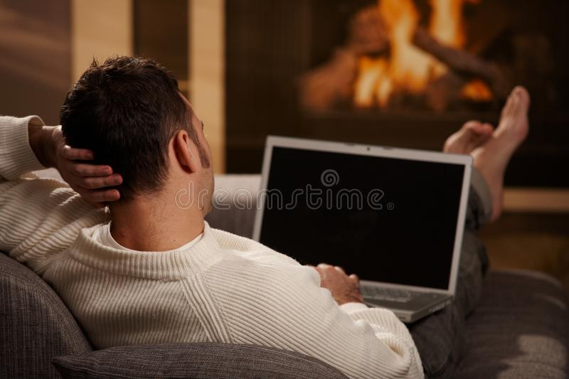 Man working at home. Man sitting on sofa at home in front of fireplace and using laptop computer, rear view
