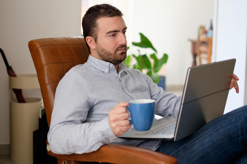 Man working at home using his laptop and drinking coffee royalty free stock photo