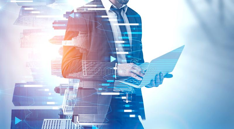 Man working with laptop in city, digital graph. Unrecognizable businessman working with laptop over cityscape background with double exposure of forex graphs stock images