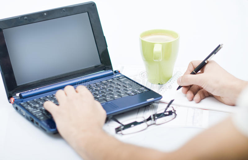 Man working on laptop with coffee and agenda royalty free stock photography