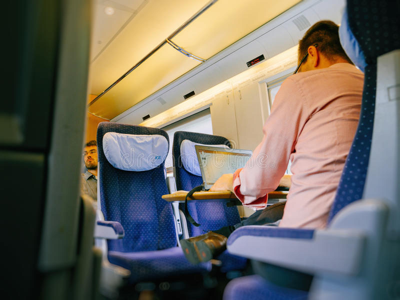 Man working on laptop in fast train stock image