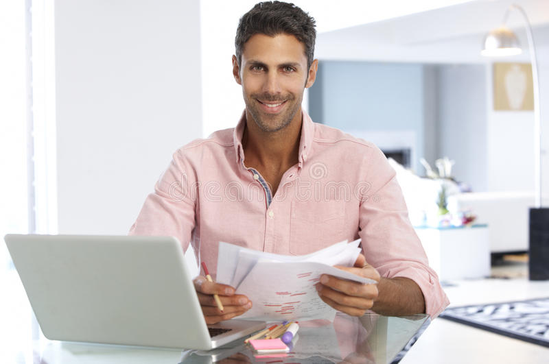 Man Working At Laptop In Home Office stock images