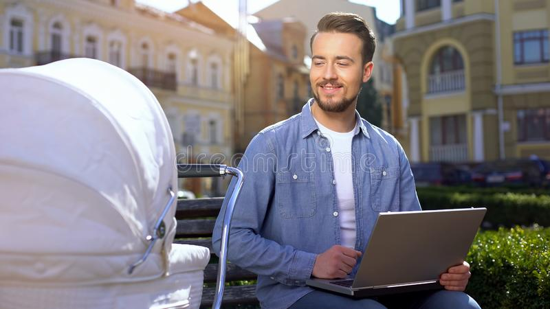 Man working laptop and smiling to infant in carriage, multitasking, freelance royalty free stock photos