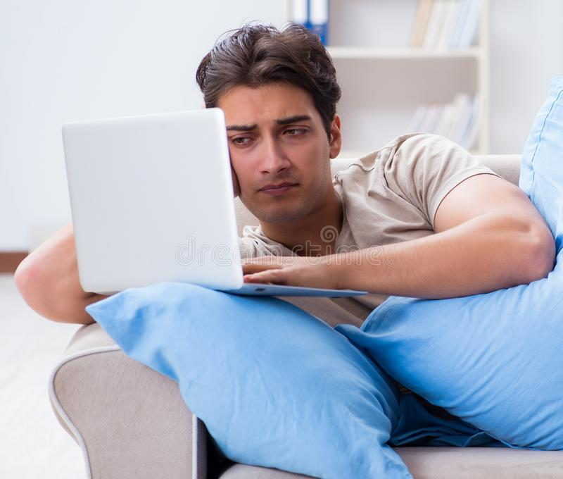 Man working late at his laptop at home stock image
