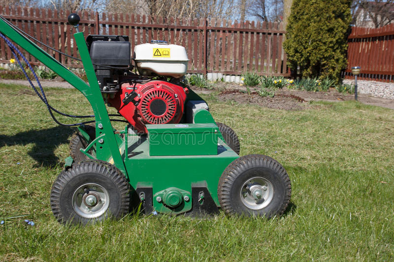 Man working with Lawn Aerator. Lawn Aerator.A lawn aerator is a garden tool or machine designed to aerate the soil in which lawn grasses grow stock image