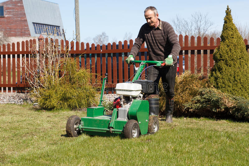 Man working with Lawn Aerator. Lawn Aerator. A lawn aerator is a garden tool or machine designed to aerate the soil in which lawn grasses grow stock images