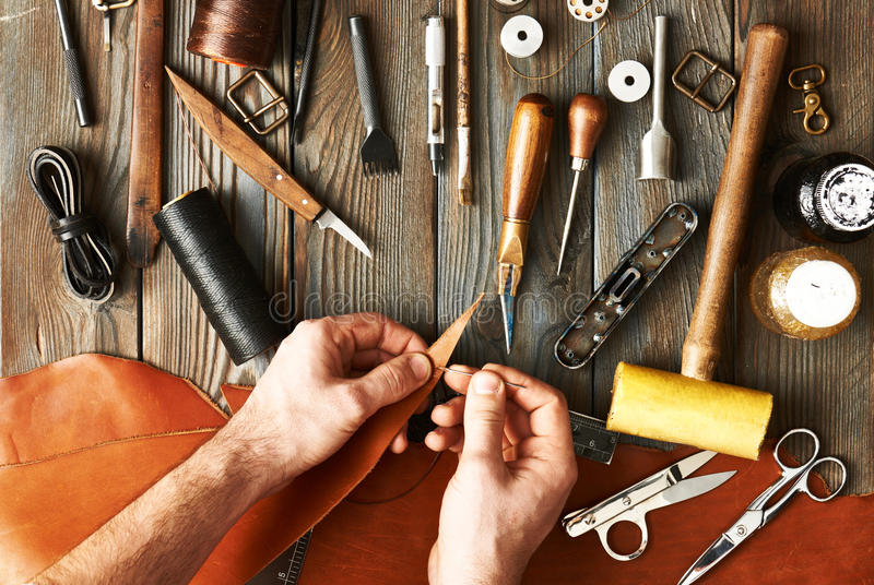 Man working with leather. Using crafting DIY tools royalty free stock photos