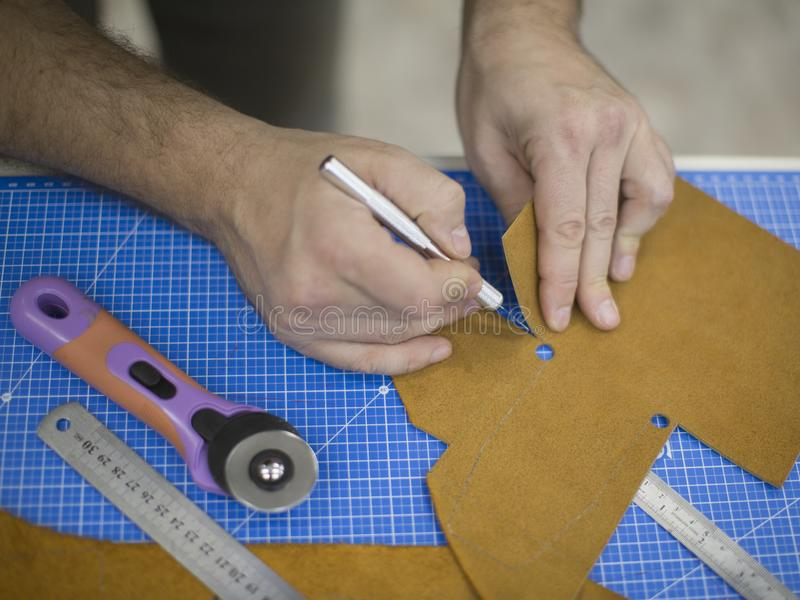 Man working with leather using crafting tools. Close up view of males hands cutting leather.  stock photos