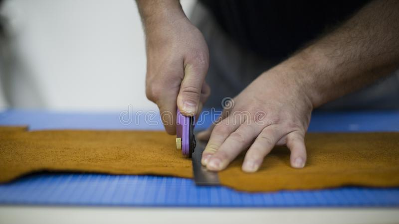 Man working with leather using crafting tools. Close up view of males hands cutting leather.  royalty free stock images