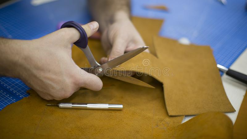 Man working with leather using crafting tools. Close up view of males hands cutting leather.  royalty free stock photography