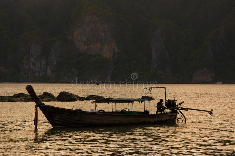 Man on long-tail taxi boat on sunset. Man working on long-tail taxi boat on sunset. Cliffs background royalty free stock photography
