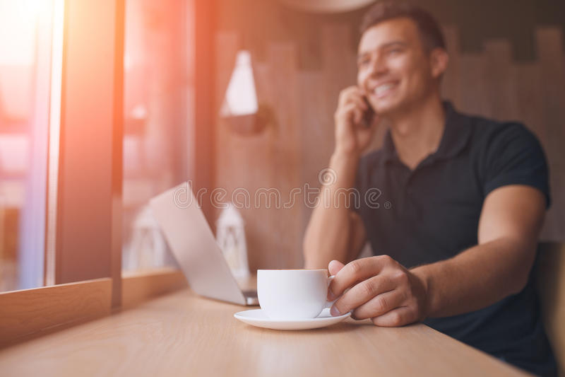 Man working on net-book in a cafe, flare sun stock photo