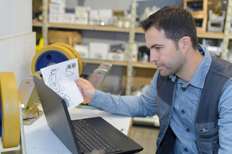 Man working with new laptop and checking instructions. Instructions royalty free stock photo