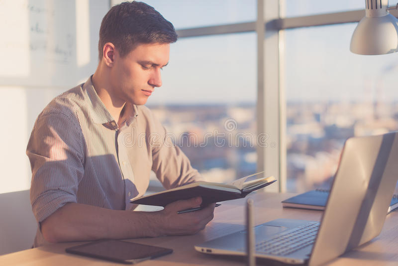 Man working in office, planning work tasks, writing down his schedule to planner at the workplace. Young woman working as an office manager, planning work tasks royalty free stock photos