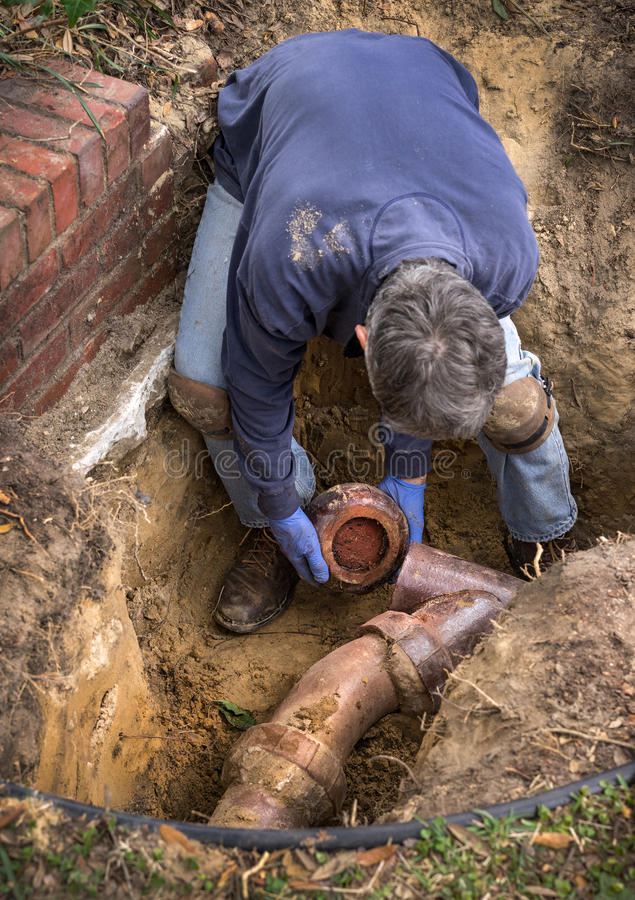 Man Working on Old Clay Ceramic Sewer Line Pipes. Man removing sections of old clogged clay ceramic sewer pipe in trench in the ground royalty free stock photo