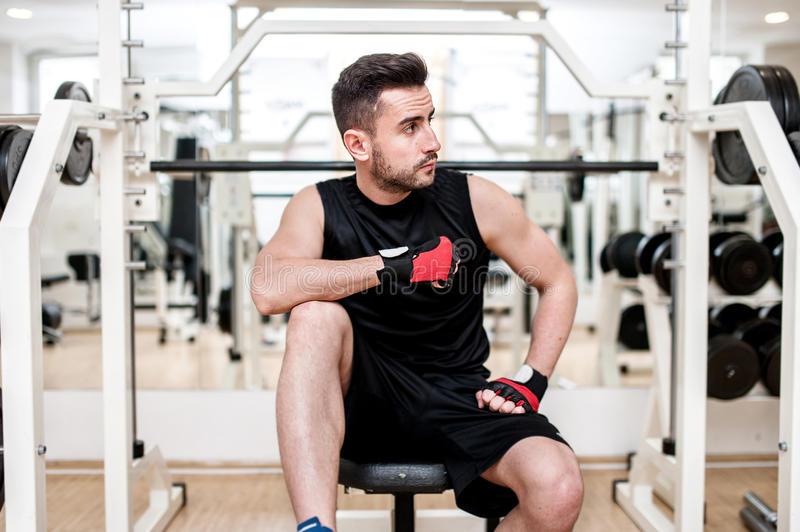 Man working out at gym, resting at bench press stock photos