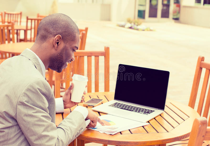 Man working outdoors reading documents using laptop stock images