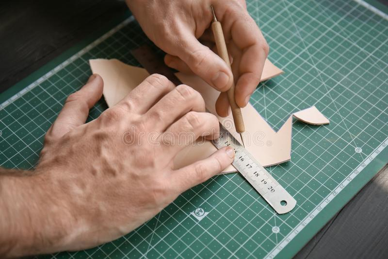 Man working with piece of leather at factory, closeup royalty free stock photos