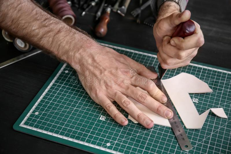 Man working with piece of leather at factory, closeup stock photo