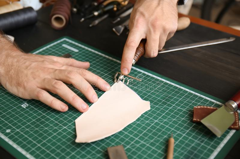 Man working with piece of leather at factory, closeup royalty free stock photography