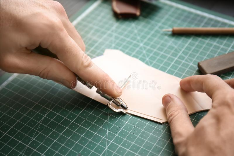 Man working with piece of leather at factory, closeup royalty free stock images