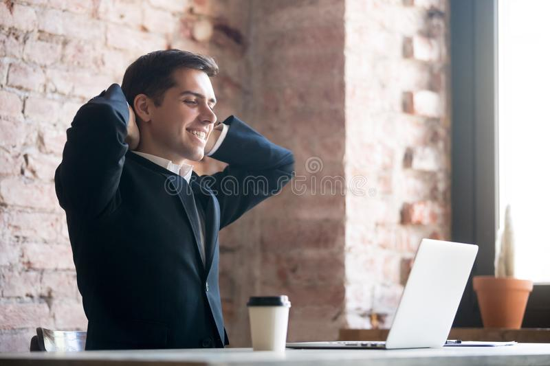 Man working and relaxing in office, end of working day. Relaxed glad businessman or business owner in suit holding hands behind head looking at computer and stock photos