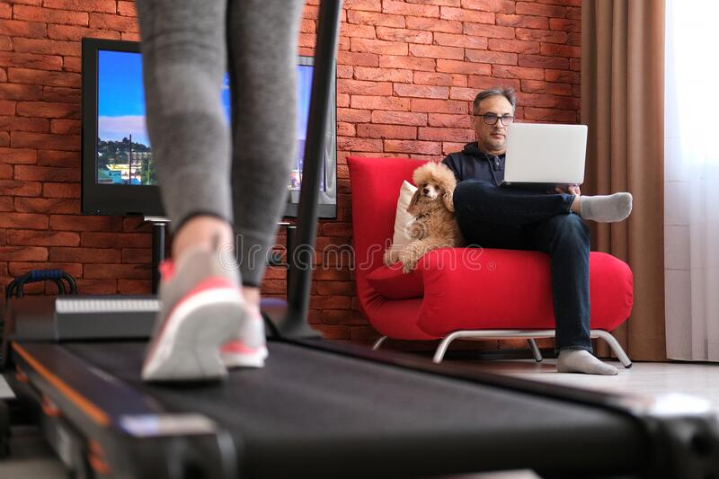 The man is working remotely. Woman exercising on a treadmill at home. Healthy lifestyle. Family at home at quarantine isolation period during coronavirus royalty free stock photography