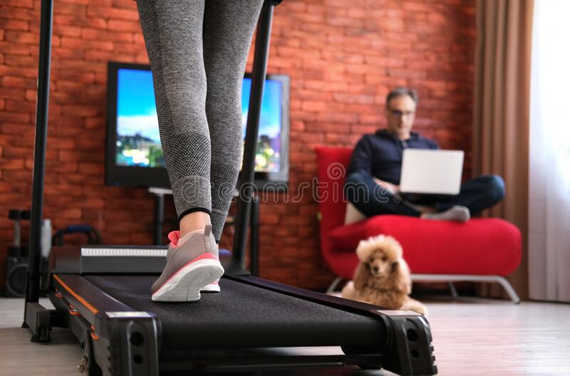The man is working remotely. Woman exercising on a treadmill at home. Healthy lifestyle. Family at home at quarantine isolation period during coronavirus royalty free stock photo