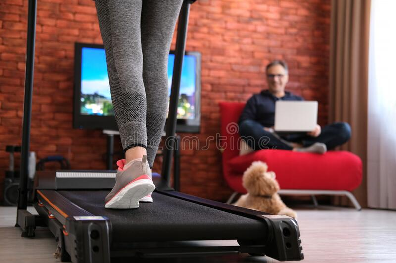 The man is working remotely. Woman exercising on a treadmill at home. Healthy lifestyle. Family at home at quarantine isolation period during coronavirus stock photography