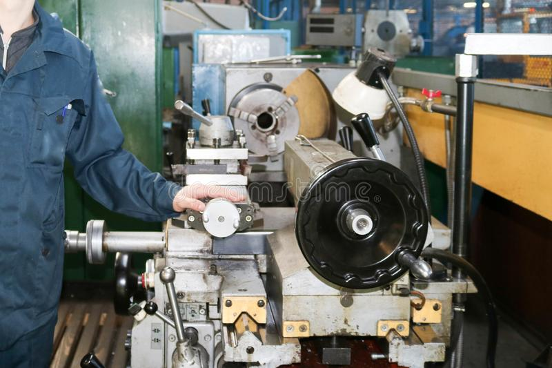 A man working in a robe, overalls stands next to an industrial lathe for cutting, turning knives from metals, wood other materials stock images